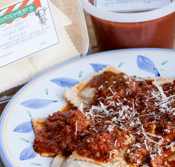 Raviloi and red sauce in shipped container with it put together on a plate