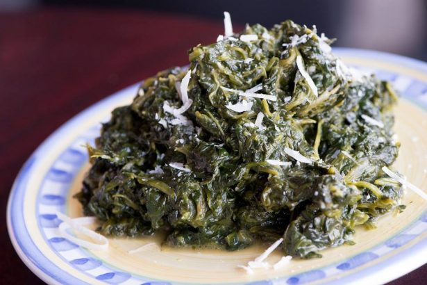 spinach on a plate with Parmesan on it