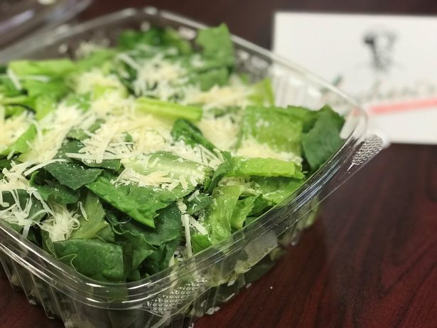 A Caesar salad in a to-go container